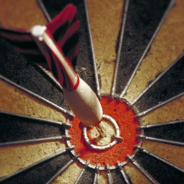 """Dart in bulls eye of a dart board."" stock image"