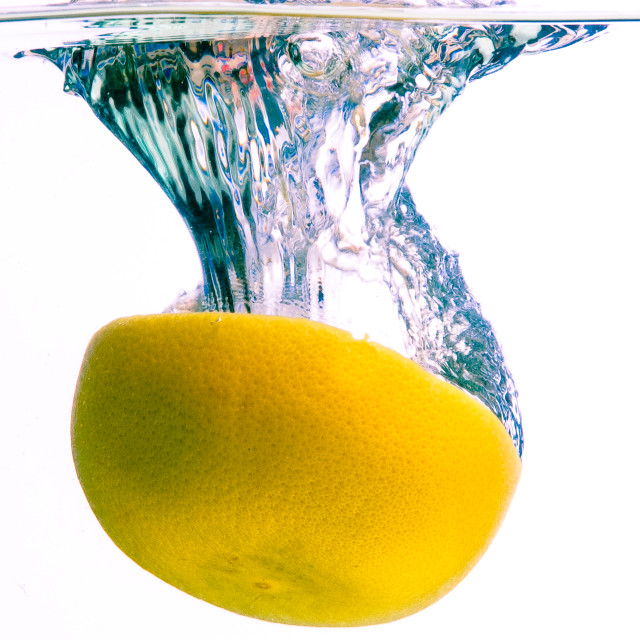 """Grapefruit falls into water with splash"" stock image"