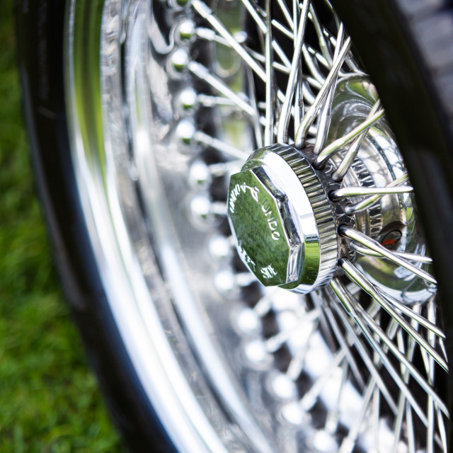 """Spoked shiny wheel in classic car"" stock image"