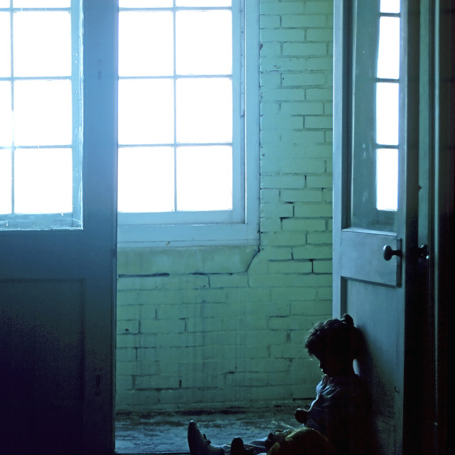 """Small child sits alone in the dark , dirty hallway of a rundown apartment building."" stock image"