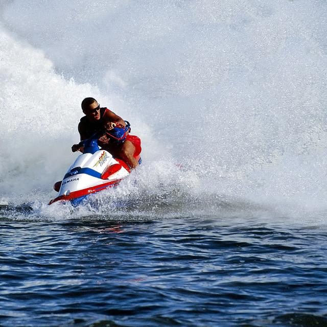 """Man on a wave runner creates huge wave."" stock image"