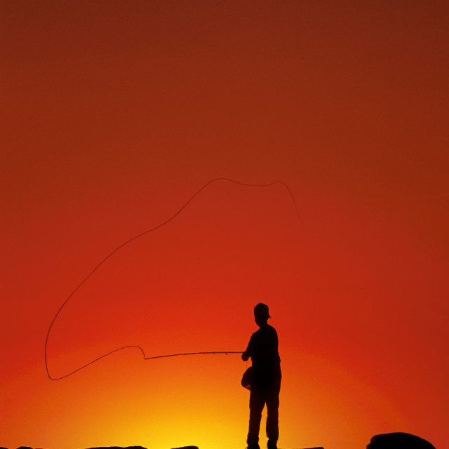 """Boy fishing from a jetty at sunset, Menemsha, Martha's Vineeyard"" stock image"