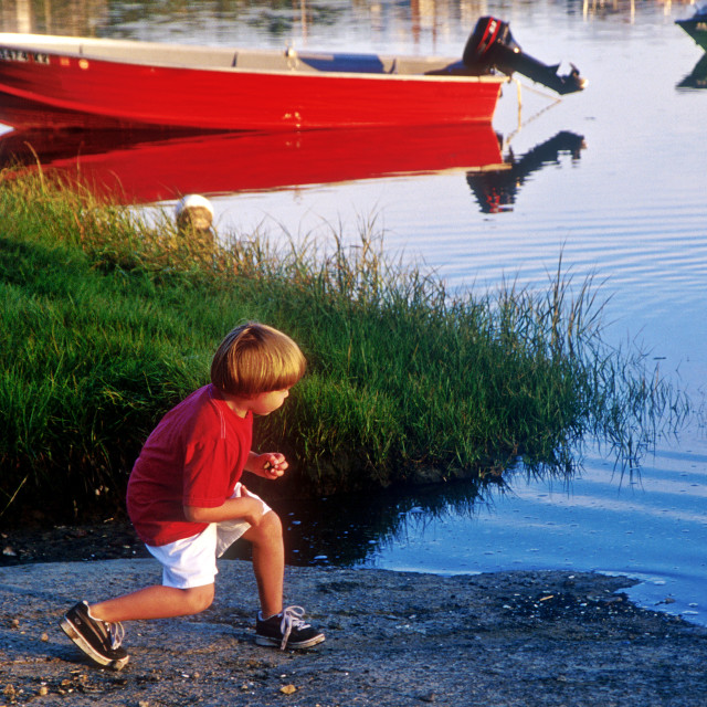 """""""Boy skips rocks at the harbor, Orleans, Cape Cod"""" stock image"""