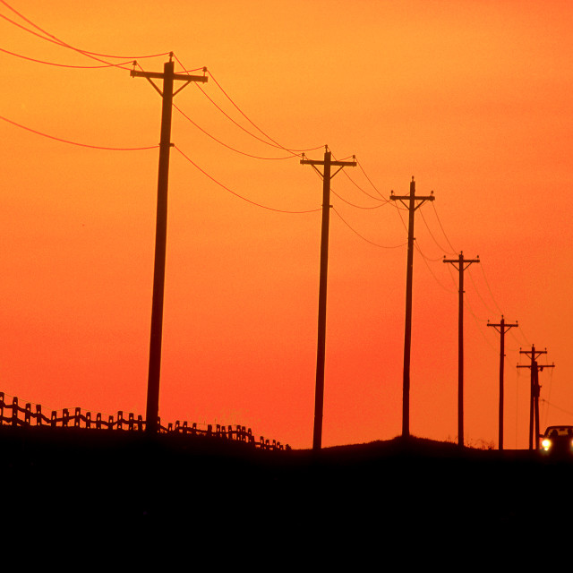 """The distant headlights of a lone aproaching car as it travels over a country road, past an expanse of telephone lines and poles in silhouette under a sunset sky"" stock image"