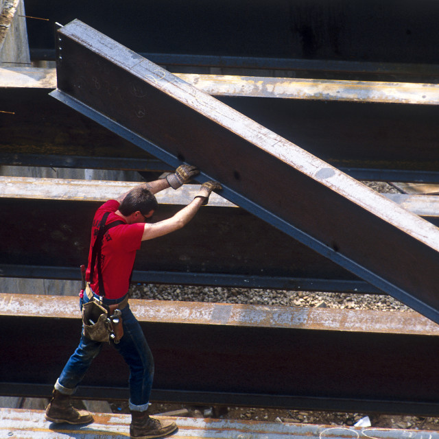 """""""Overview of a construction worker guiding a steel beam on a commercial building work site."""" stock image"""