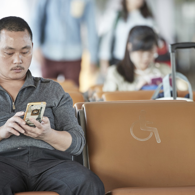 """Chinese man with cellphone sitting in airport terminal"" stock image"