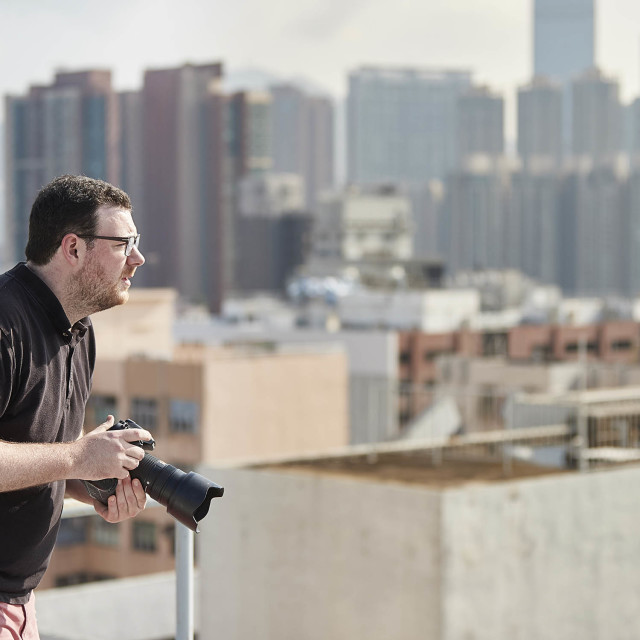 """Photographer on rooftop above Hong Kong"" stock image"