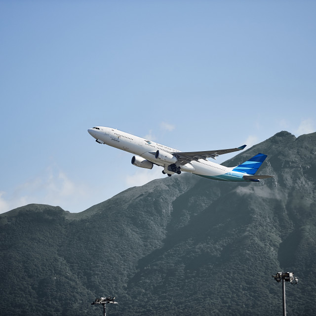 """Passenger jet aircraft taking off in front of mountains"" stock image"
