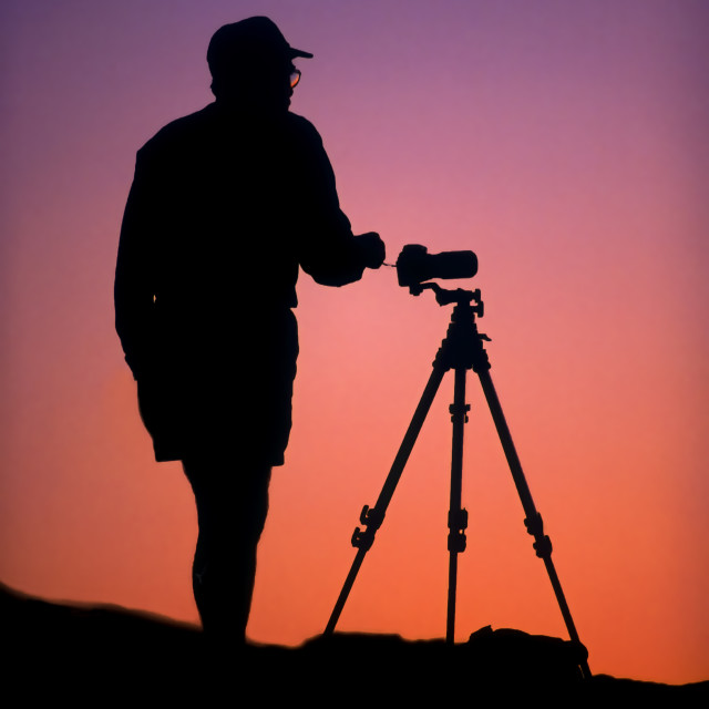 """""""A photographer and camera tripod in silhouette at dawn."""" stock image"""