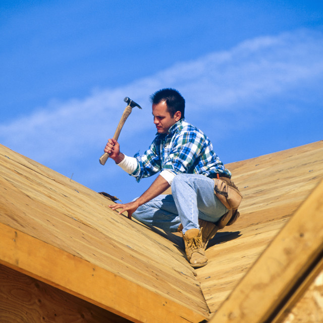 """""""Construction worker on roof of new house construction."""" stock image"""