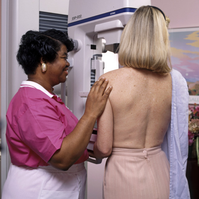 """""""Tech assists patient undergo a mammography test."""" stock image"""