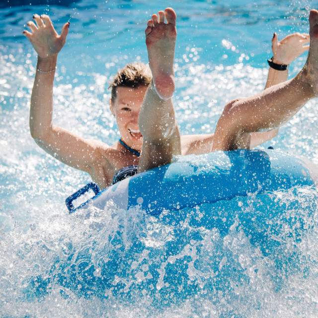 """Funny couple taking a fast water ride on a float splashing water. Summer vacation concept."" stock image"