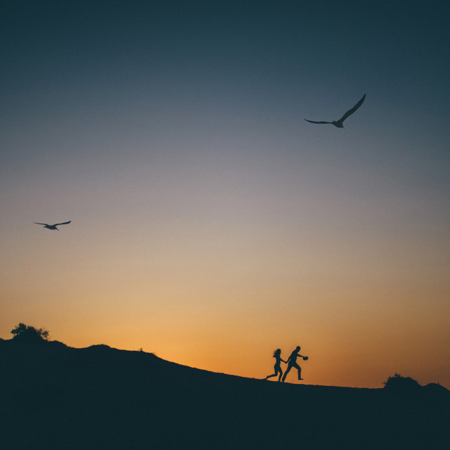 """Silhouette of happy couple running at sunset"" stock image"