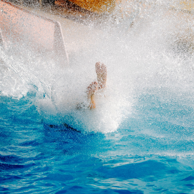 """""""Slide on the water slide feet first with splashes"""" stock image"""