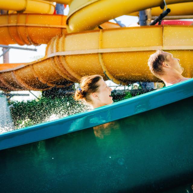 """Happy Couple Enjoying Water Slide in swimming pool"" stock image"