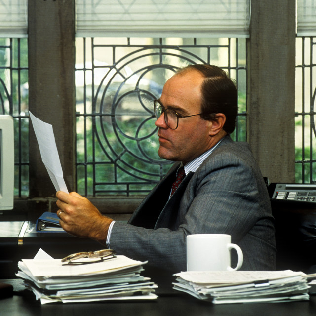 """""""Executive reviews paperwork in his corporate office."""" stock image"""