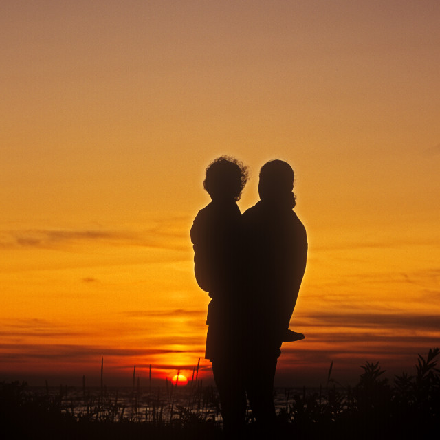 """""""Silhouetted woman holding child while watching the sunset."""" stock image"""