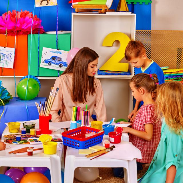 """Children with teacher woman painting on paper in kindergarten ."" stock image"