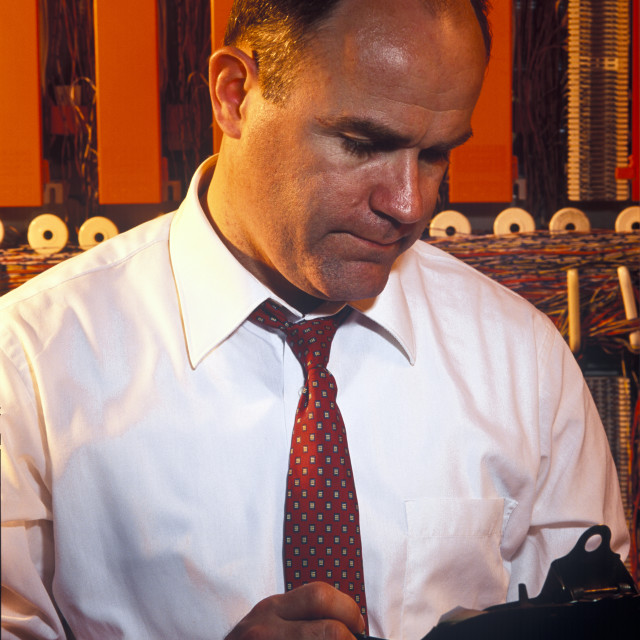 """Manager inspecting telaphone communications installation."" stock image"