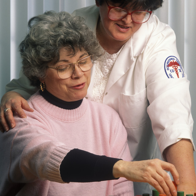 """""""Physical therapist with patient working on motor skills at a peg board. Occupational threapy."""" stock image"""