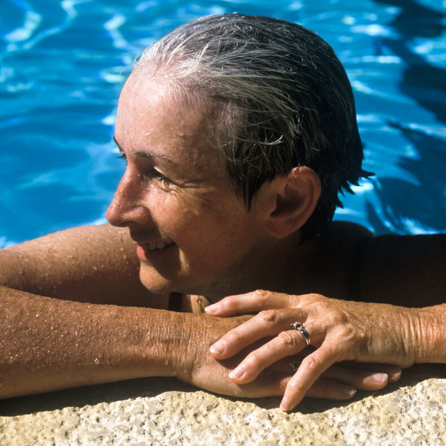 """""""Senior women rests after a swim in the pool."""" stock image"""