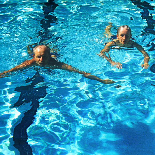 """""""Senior couple swimming laps in a pool."""" stock image"""