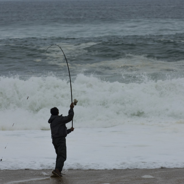 """""""Fisherman launching his line from the edge of the ocean"""" stock image"""