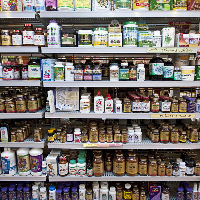 """Vitamin and herbal supplement display shelves in a health food store."" stock image"