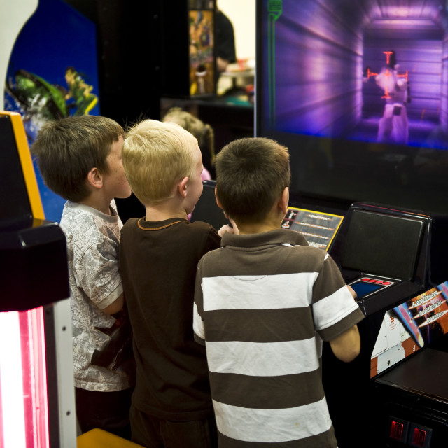 """Boys playing a video game in an arcade."" stock image"