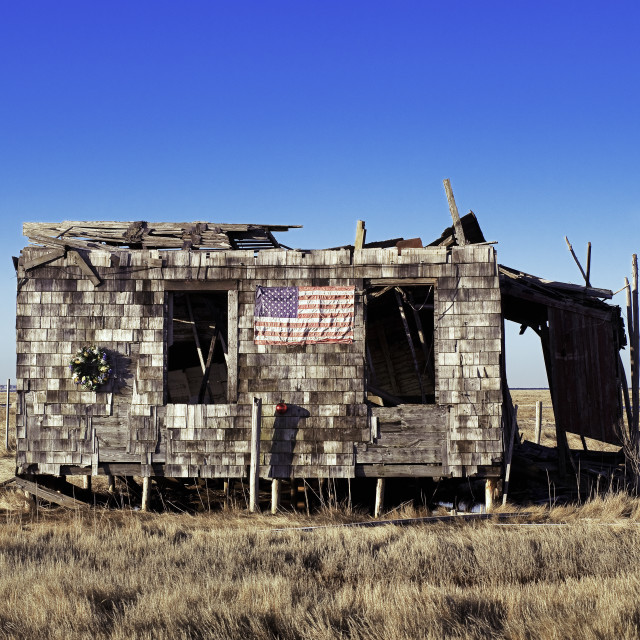 """Ruined and abondoned shack with American flag and Christmas wreath."" stock image"