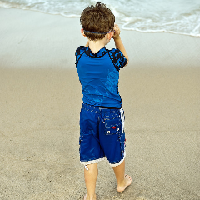 """""""Young boy with goggles enjoys the ocean water."""" stock image"""