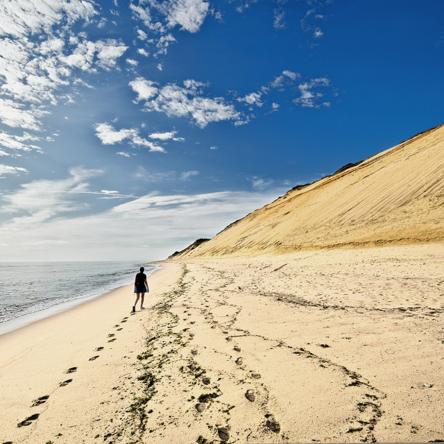 """Woman walking on beach along huge sand dune cliffs at Long Nook Beach, Cape Cod National Seashore, Truro, Cape Cod, Massachusetts, USA."" stock image"