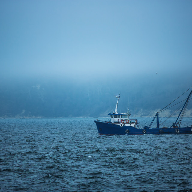 """Trawler fishing boat sailing in open waters on a cold and foggy"" stock image"