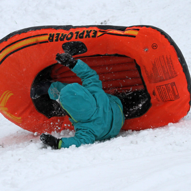 """Child sledding on dingy in snow."" stock image"