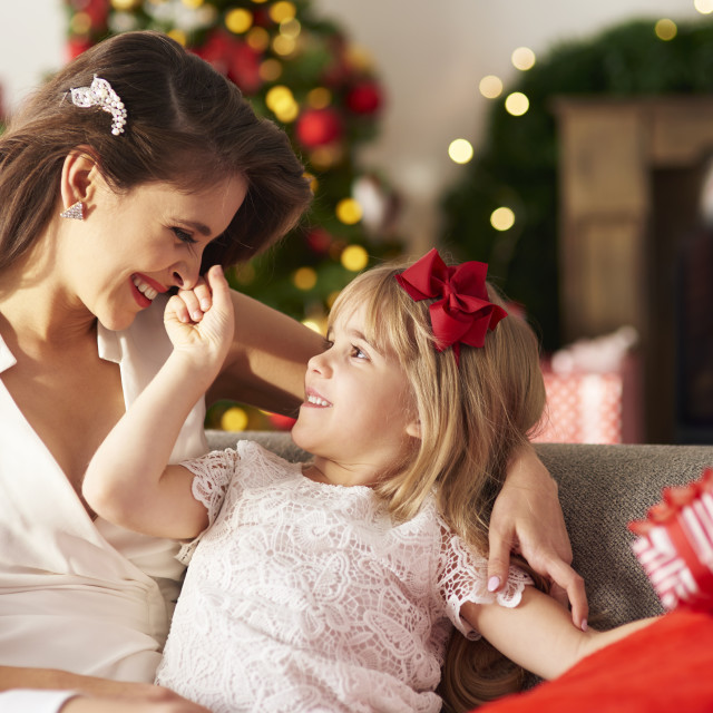 """Daughter teasing mummy by catching her nose."" stock image"