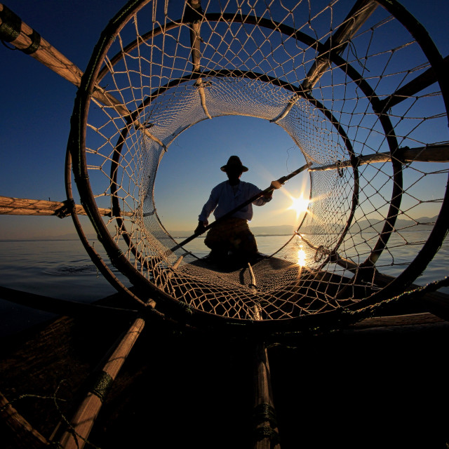 """Intha fisherman against the sunset sky"" stock image"