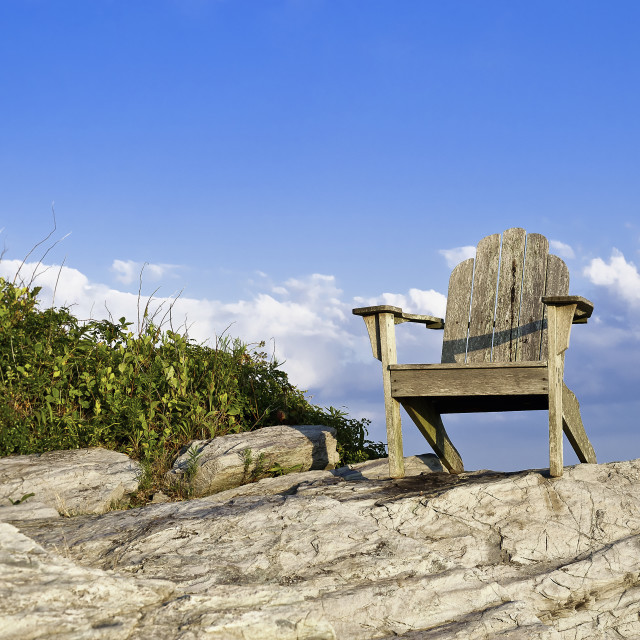 """""""Adirondack chair sits on a rocky perch with a scenic coastal view, Newport, RI, Rhode Island"""" stock image"""