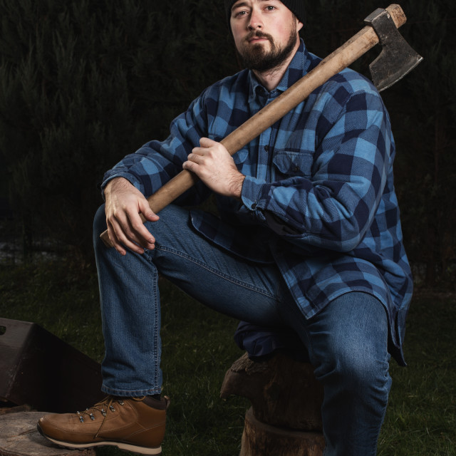 """lumberjack sitting on log with an ax on shoulder"" stock image"