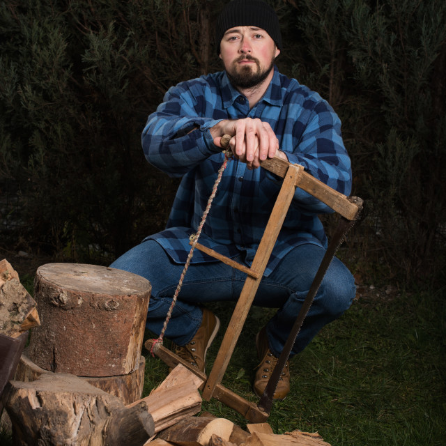 """lumberjack sitting on log with saw in hands"" stock image"