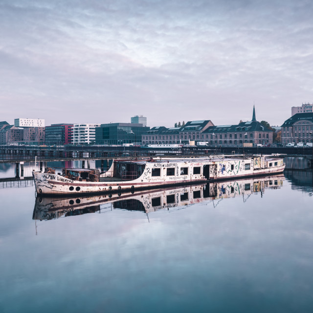 """Skyline of East-Berlin with an abandoned ship in the foreground"" stock image"