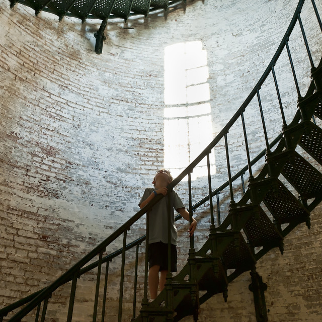 """""""Boy marvels at the interieor of a lighthouse, Corolla Lighthouse, Outer Banks, NC, North Carolina"""" stock image"""