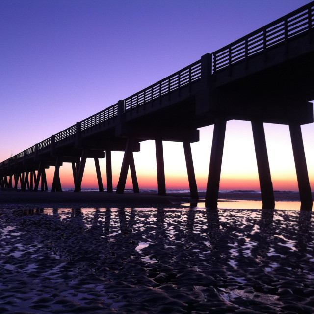 """The brilliant colors of sunrise bathe an early morning view of Jacksonville Beach Pier in North Florida. USA."" stock image"