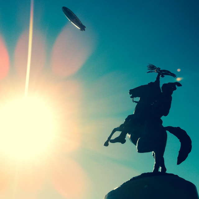 """""Unconquered"" Seminole statue outside Florida State University's Doak Campbell Stadium with Goodyear blimp overhead."" stock image"