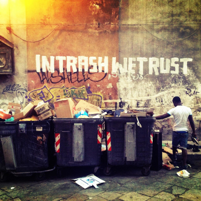 """""""Man Collecting things from the rubbish bin, on the wall: """"in trash we trust"""", Palermo, Italy"""" stock image"""