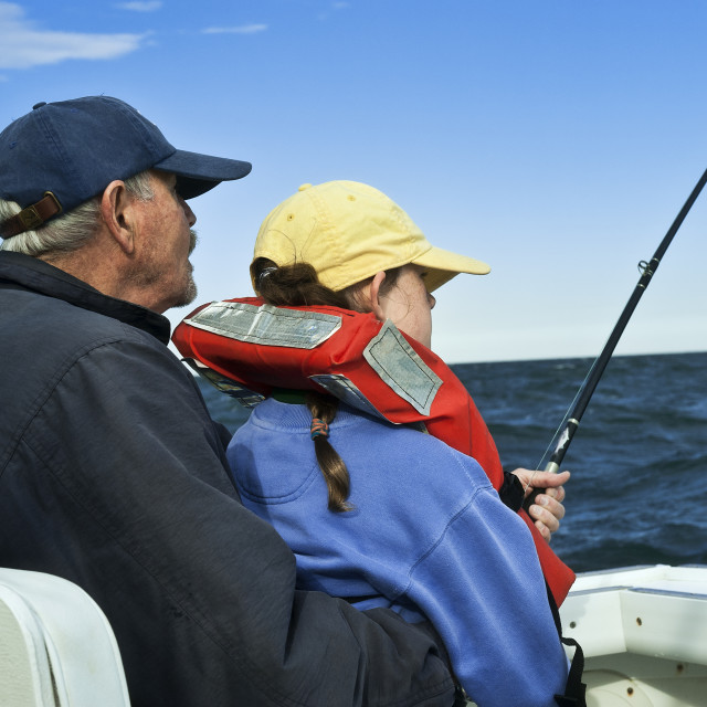"""Senior man teaching grand daughter to fish."" stock image"