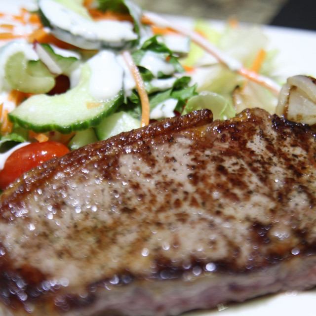 """A well cooked steak on a white plate with salad"" stock image"