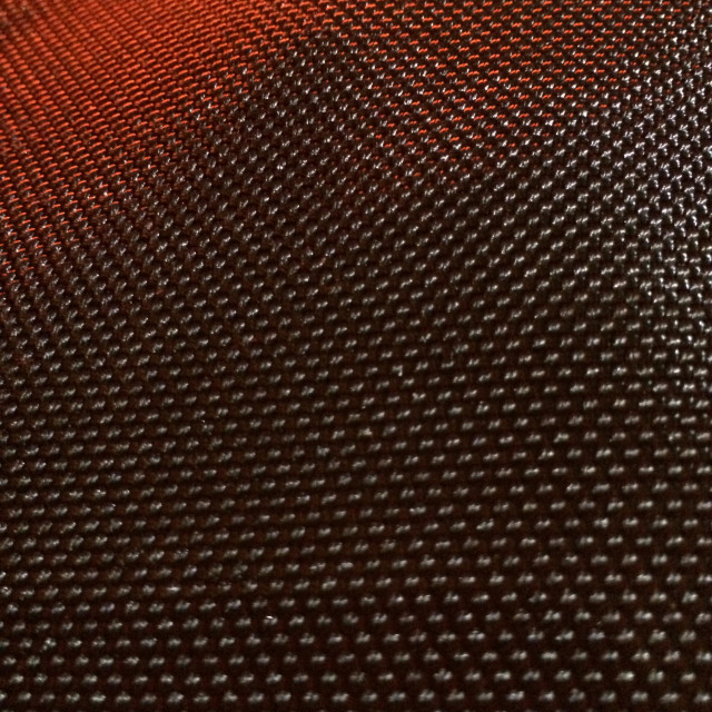 """The texture of heavy woven black nylon fabric partially illuminated by orange light."" stock image"