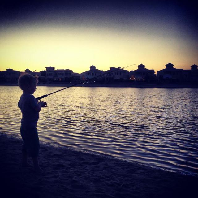 """Boy fishing, sunset, Dubai"" stock image"