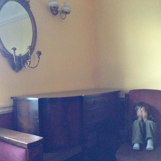 """Child hiding in old room"" stock image"