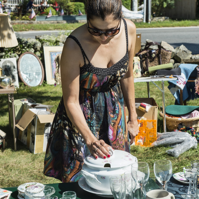 """""""Woman shopping for bargains at a garage sale."""" stock image"""